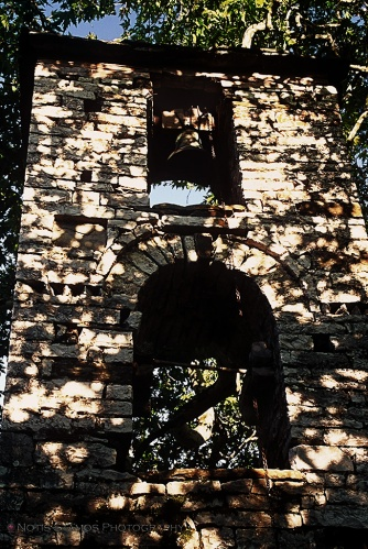 Bell tower in the forest hit by strong sunlight at midday.